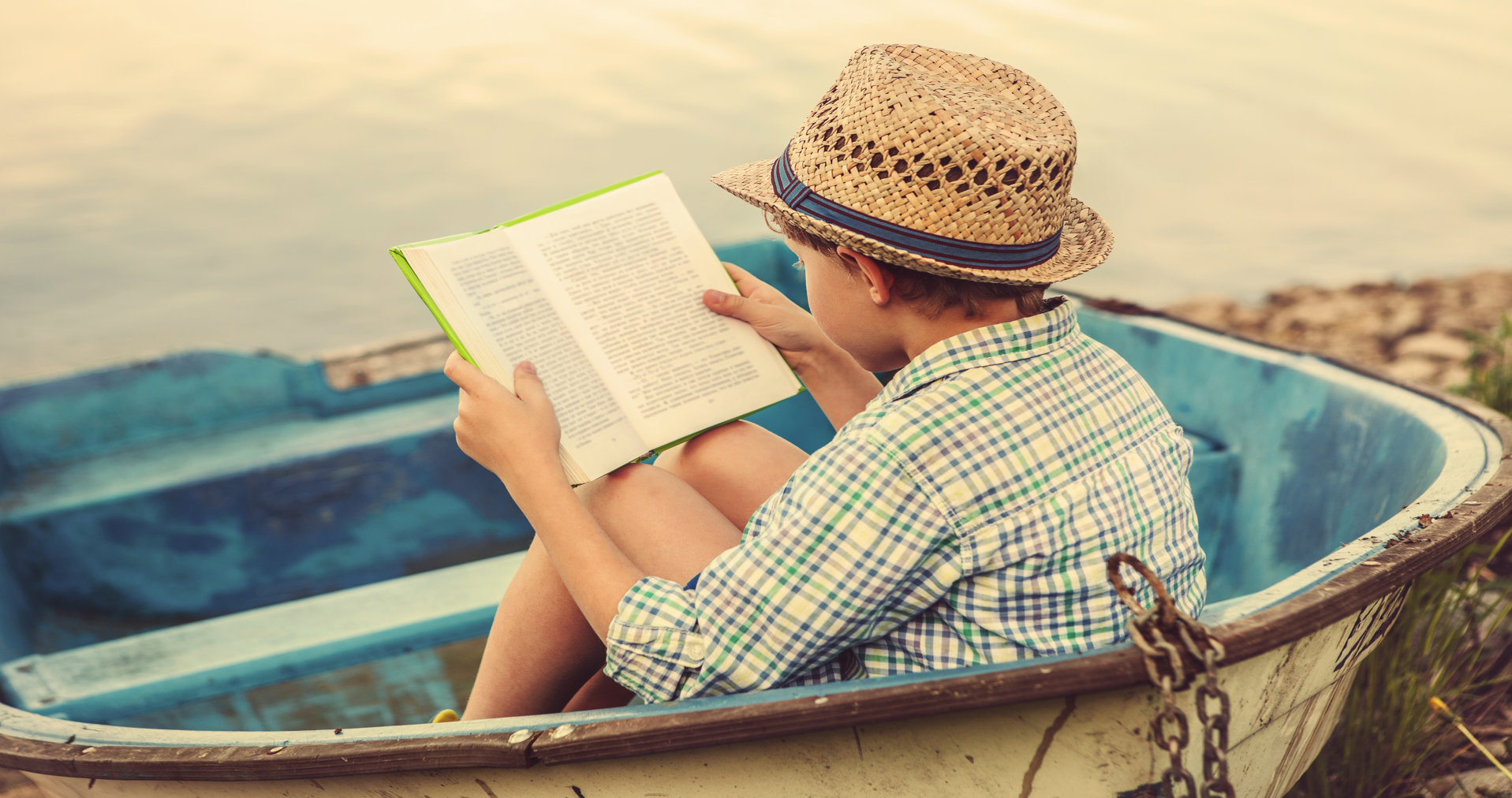 Young_boy_reading_in_boat